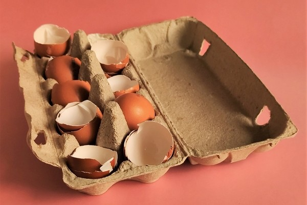 Broken eggs in a cardboard egg carton.